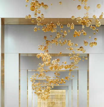 Over 5000 golden baubles have each been hand strung and hung in the art gallery inspired showroom